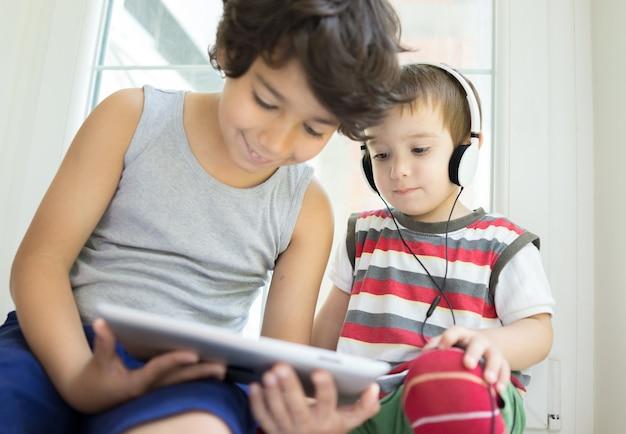 Twee kleine broers die samen op tablet thuis spelen