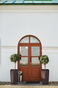 Twee kleine decoratieve bomen aan weerszijden van een ingang van de voordeur van het europese café
