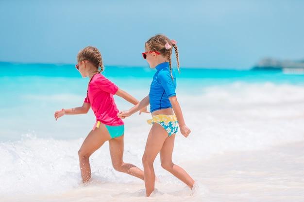 Twee kleine gelukkige meisjes hebben veel plezier op tropisch strand terwijl ze samen spelen