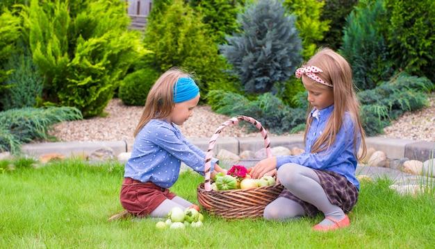 Twee kleine gelukkige meisjes met grote herfstoogst van tomaten in manden