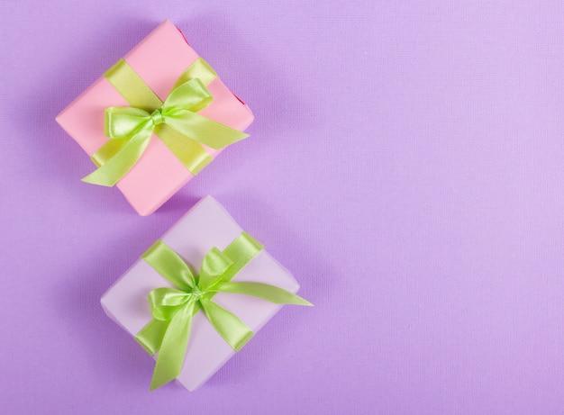 Twee kleine geschenkdoos met een strik op een paarse achtergrond.