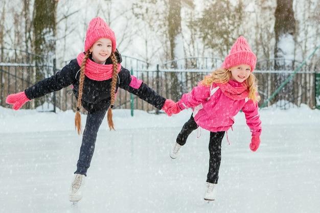 Twee kleine glimlachende meisjes schaatsen op ijs in roze slijtage en handgemaakte sjaals.