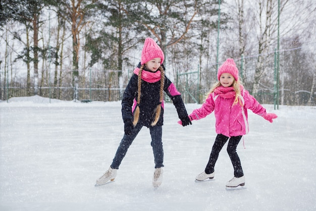 Twee kleine glimlachende meisjes schaatsen op ijs in roze slijtage.