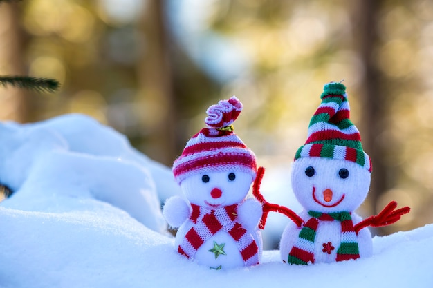 Twee kleine grappige sneeuwman van de speelgoedbaby in gebreide hoeden en sjaals in diepe sneeuw in openlucht op heldere blauwe en witte exemplaar ruimteachtergrond. gelukkig nieuwjaar en merry christmas wenskaart.