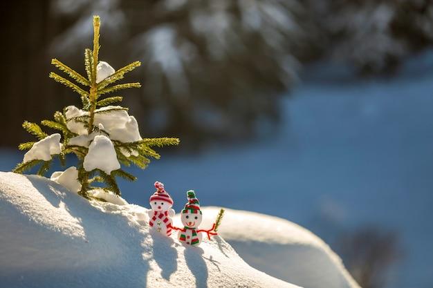Twee kleine grappige sneeuwpop van de speelgoedbaby in gebreide hoeden en sjaals in diepe sneeuw in openlucht dichtbij de tak van de pijnboomboom.