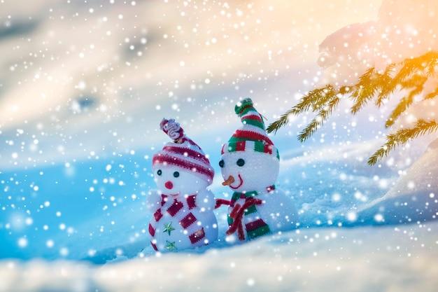 Twee kleine grappige speelgoed baby sneeuwpop in gebreide mutsen en sjaals in diepe sneeuw buiten op helderblauwe en witte kopie ruimte achtergrond. gelukkig nieuwjaar en merry christmas wenskaart.
