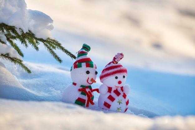 Twee kleine grappige speelgoed baby sneeuwpop in gebreide mutsen en sjaals in diepe sneeuw buitenshuis