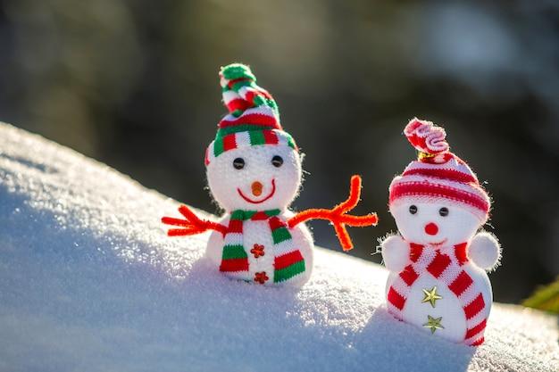 Twee kleine grappige speelgoed baby sneeuwpop in gebreide mutsen