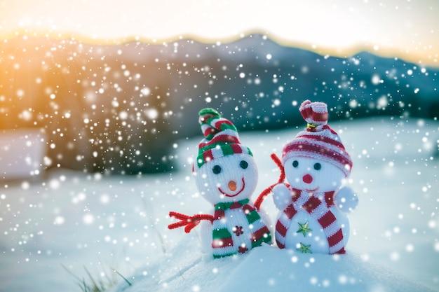 Twee kleine grappige speelgoed babysneeuwman in gebreide mutsen en sjaals in diepe sneeuw buiten op de wazige achtergrond van het bergenlandschap. gelukkig nieuwjaar en merry christmas wenskaart thema.