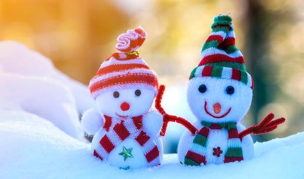 Twee kleine grappige speelgoed babysneeuwman in gebreide mutsen en sjaals in diepe sneeuw buiten op helder blauw en wit exemplaar ruimte oppervlak