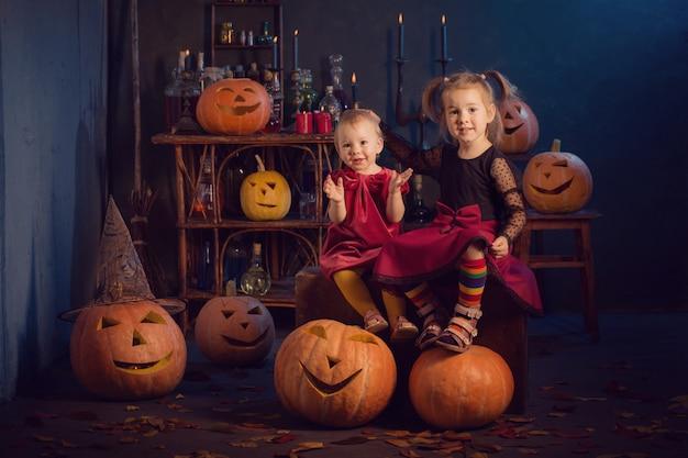 Twee kleine heksen met halloween-pompoenen binnen
