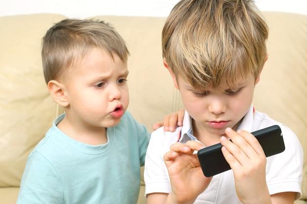 Twee kleine jongen kijken naar de smartphone. de relaties tussen kinderen en moderne gadgets