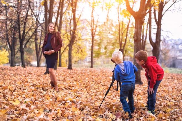 Twee kleine jongen met een grote reflexcamera op een statief. maak een foto van hun zwangere moeder. familie fotosessie