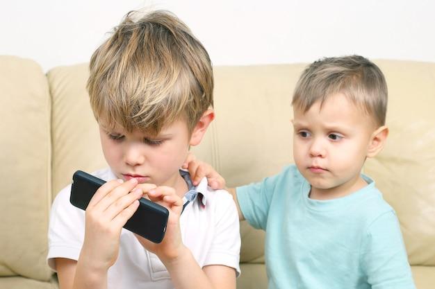 Twee kleine jongens kijken naar mobiele telefoon. de relaties tussen kinderen en moderne gadgets