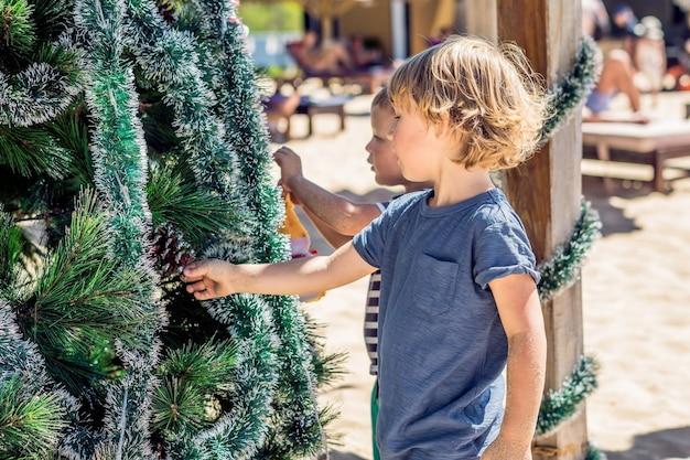 Twee kleine jongens met kerstmis op het strand