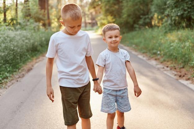 Twee kleine jongens met witte t-shirts en korte broeken die samen gaan en handen vasthouden in het zomerpark, broers die buiten lopen en positieve emoties uitdrukken.