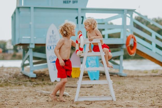Twee kleine jongens poseren bij de strandwachtstoel op het strand