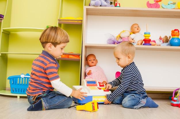 Twee kleine jongens spelen in de rol van kassier en koper in de kleuterschool