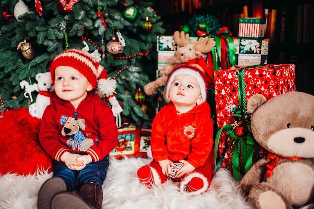 Twee kleine jongens zitten onder cadeautjes voor een kerstboom