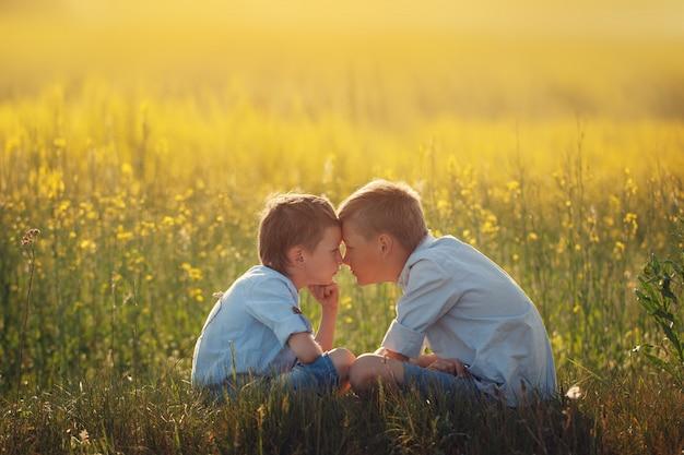Twee kleine jongensvrienden kijken elkaar op de zonsondergangzomer.