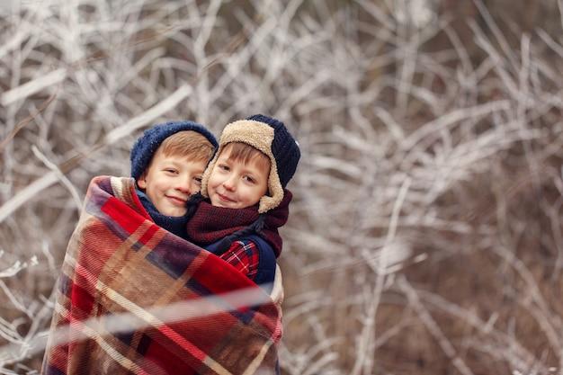 Twee kleine jongensvrienden koesteren onder warme deken in de winterbos. . broerderliefde. concept vriendschap