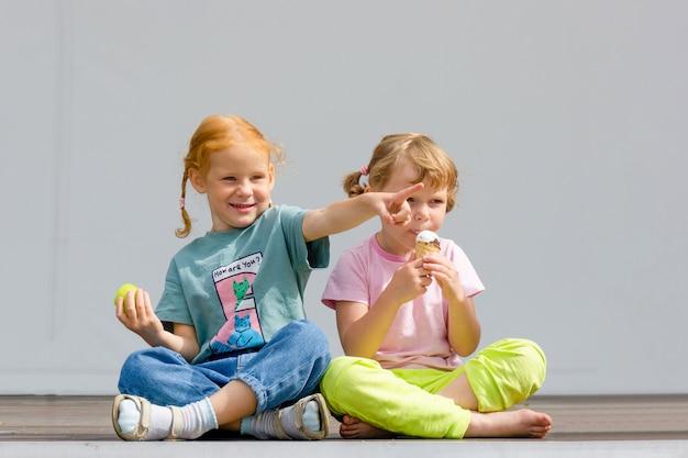 Twee kleine kaukasische schattige meisjes zitten in kleermakerszit en eten ijs.