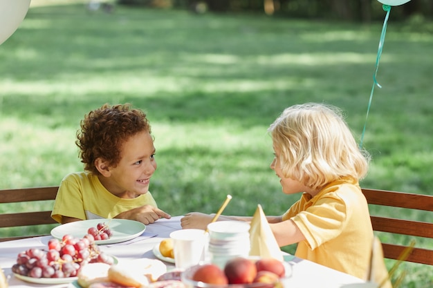 Twee kleine kinderen aan picknicktafel buiten versierd met ballonnen voor verjaardagsfeestje in de zomer kopiëren s...