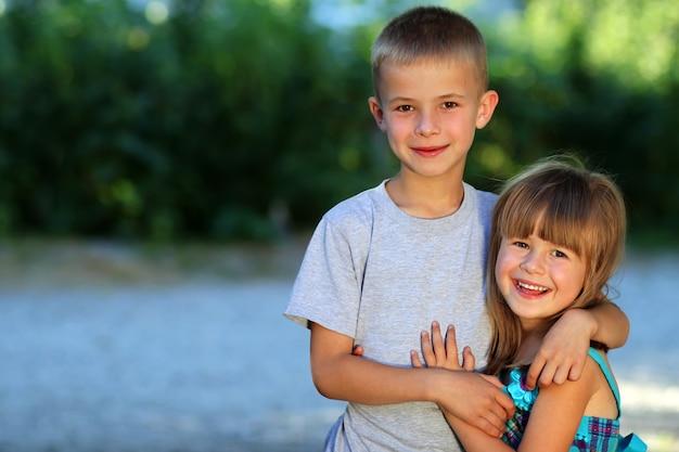 Twee kleine kinderen broer en zus samen. meisje in jurk knuffelen jongen. familie relaties concept.