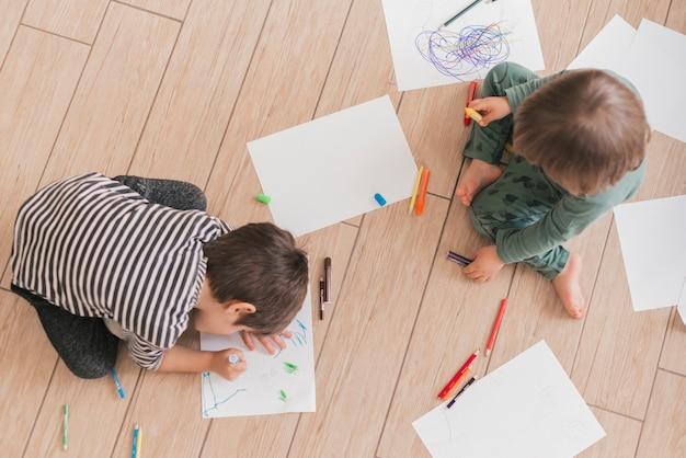 Twee kleine kinderen die samen schilderen