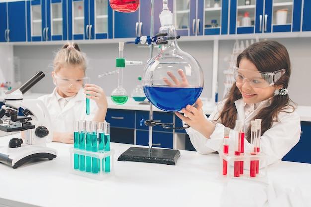 Twee kleine kinderen in laboratoriumjas het leren van chemie in schoollaboratorium. jonge wetenschappers die in beschermende bril experimenteren in laboratorium of chemisch kabinet. ingrediënten bestuderen voor experimenten.