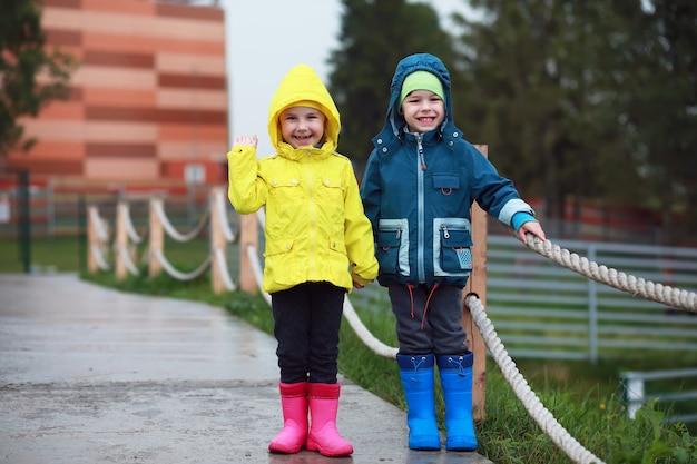 Twee kleine kinderen, jongen en meisje, kijken op een koude herfstdag naar de apenshow in de dierentuin. kinderen kijken naar dieren in safaripark.