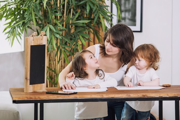 Twee kleine kinderen meisjes schattig mooi en blij met moeder thuis aan tafel zitten en tekenen