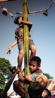 Twee kleine kinderen worstelen om naar de top te klimmen in het spel greasy pole