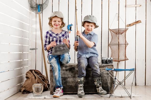 Twee kleine kinderen zitten op de borst met net en staaf in handen
