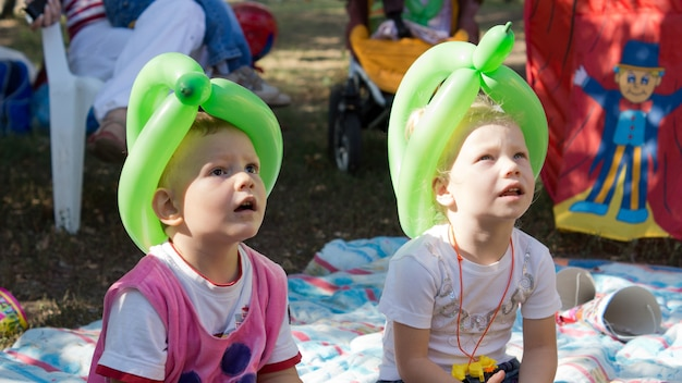 Twee kleine kinderen zitten op een kleed op de grond en dragen ballonmutsen op een feestje dat naar een poppenshow kijkt