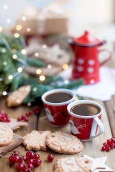 Twee kleine kopjes koffie en een koffiepot, een cake met bessen en koekjes, geschenken, in de buurt van een kerstboom op een dorpstafel bij het raam