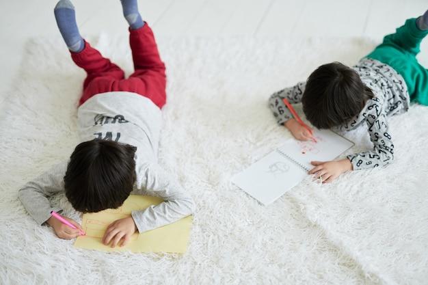 Twee kleine latijnse jongens, tweelingbroers die foto's maken met kleurrijke potloden in papieren album terwijl ze op de vloer liggen. broers en zussen die samen creatieve activiteiten ondernemen. afstandsonderwijs voor kinderen