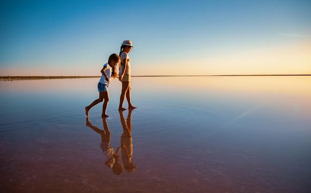Twee kleine lieve, gelukkige zussen wandelen langs het spiegelachtige roze zoutmeer en genieten van de warme zomerzon tijdens de langverwachte vakantie