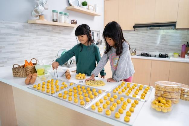 Twee kleine meisje nastar taart taart samen thuis keuken maken