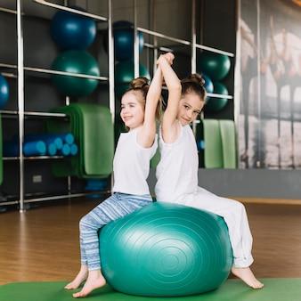 Twee kleine meisje zitten rug aan rug bij het samen oefenen van de bal