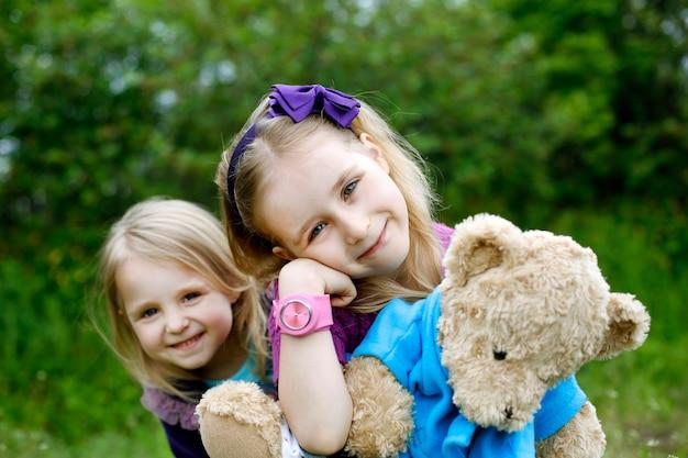 Twee kleine meisjes broers en zussen knuffelen teddybeer in de natuur