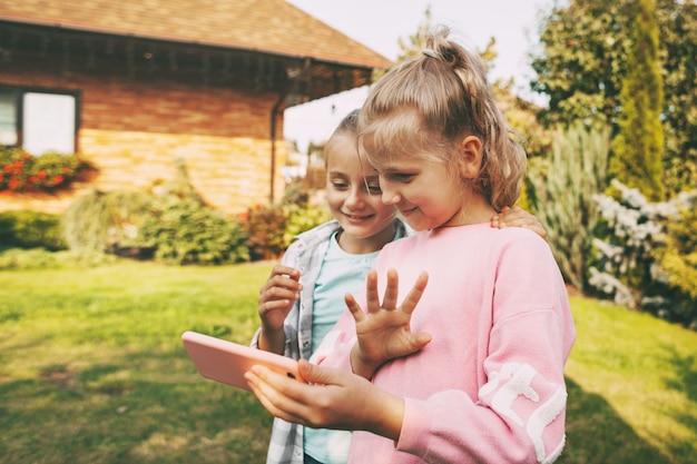 Twee kleine meisjes buiten hun huis praten op mobiele telefoon met vrienden