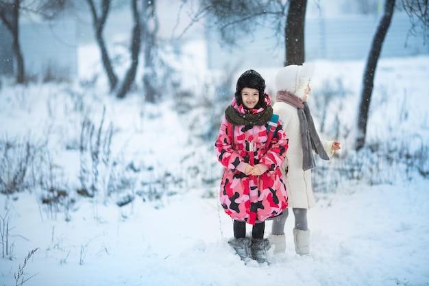 Twee kleine meisjes buiten spelen tijdens sterke sneeuwval.