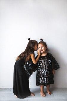 Twee kleine meisjes chatten, geïsoleerd over wit, meisjes gekleed in mama's kleren a