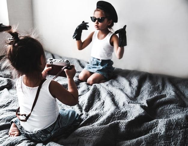 Twee kleine meisjes die een foto van elkaar maken. kleine modieuze vrouwen