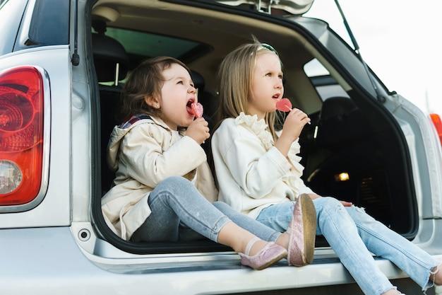Twee kleine meisjes die in de kofferbak van een auto zitten en lolly's eten