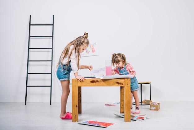 Twee kleine meisjes die met aquarelle aan tafel schilderen