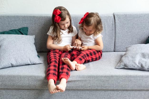 Twee kleine meisjes die op bank zitten en op smartphone spelen.
