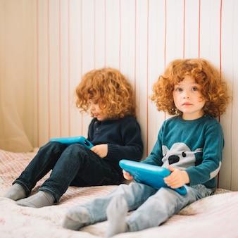 Twee kleine meisjes die op bed zitten die digitale tablet gebruiken