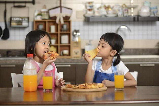 Twee kleine meisjes die pizza eten
